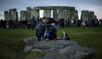 People embrace by the ancient stone circle of Stonehenge, in southern England on the annual Winter Solstice, in this Friday, Dec. 21, 2012, file photo. (AP Photo/Matt Dunham, File)