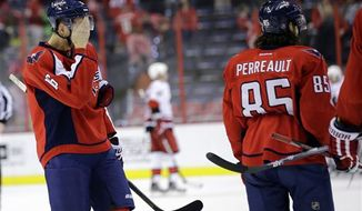 Washington Capitals right wing Eric Fehr (16) wipes his face, with center Mathieu Perreault (85) nearby, after an NHL hockey game against the Carolina Hurricanes on Tuesday, March 12, 2013 in Washington. The Hurricanes won 4-0. (AP Photo/Alex Brandon)