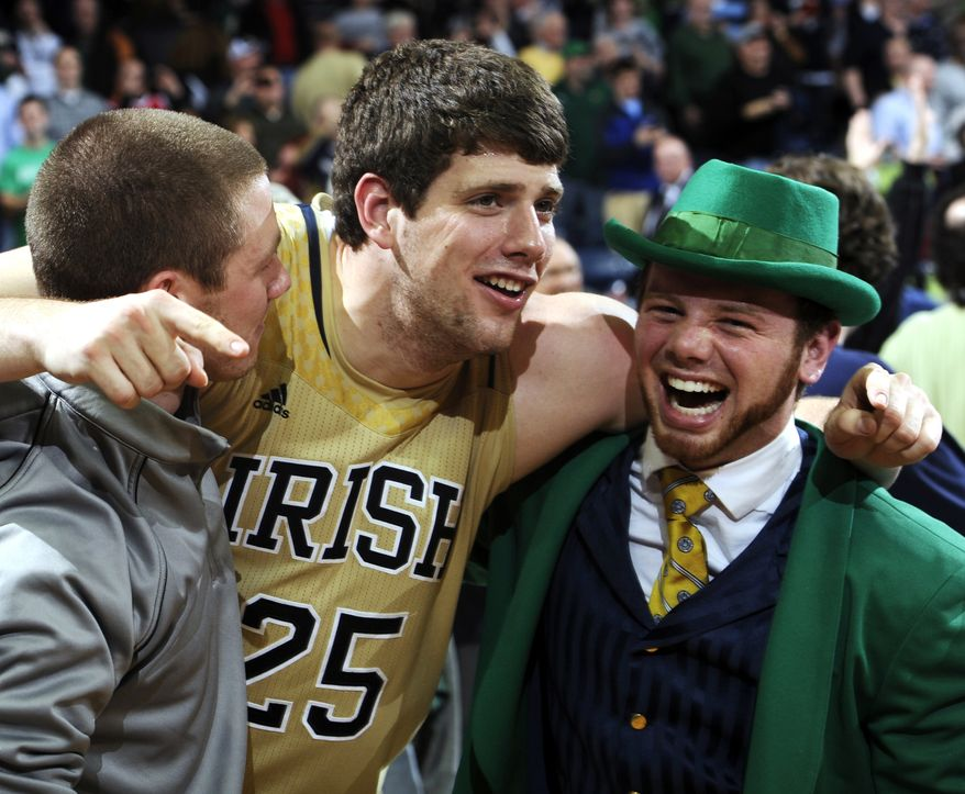 **FILE** Notre Dame forward Tom Knight (25) celebrates with Leprechaun Bryce Burton following an NCAA college basketball game against Louisville, Saturday, Feb. 9, 2013, in South Bend, Ind. Notre Dame won 104-101 in five overtimes. (AP Photo/Joe Raymond)