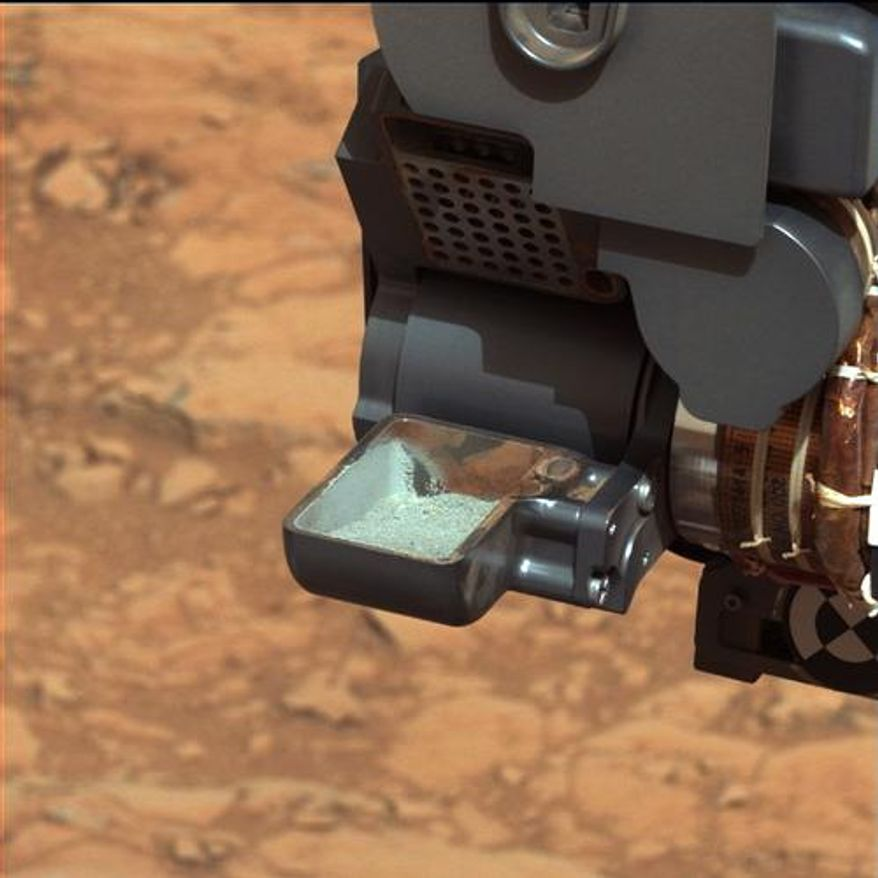 The Mars rover Curiosity holds a scoop of powdered rock. The rover recently drilled into a Martian rock for the first time and transferred a pinch of powder to its instruments to analyze the chemical makeup. (AP Photo/NASA)