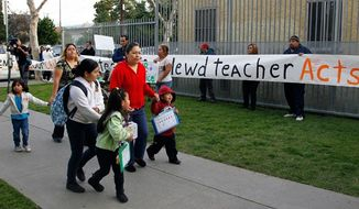 ** File ** Parents bring their children to school as others protest outside Miramonte Elementary school in Los Angeles Feb. 6, 2012.