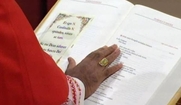 "In this image taken from video provided by CTV, a cardinal places his hands on the Gospel to ""promise pledge and swear"" to keep the oath of secrecy after entering the Sistine Chapel in Vatican City for the conclave to elect the next pope Tuesday, March 12, 2013. (AP Photo/CTV)"
