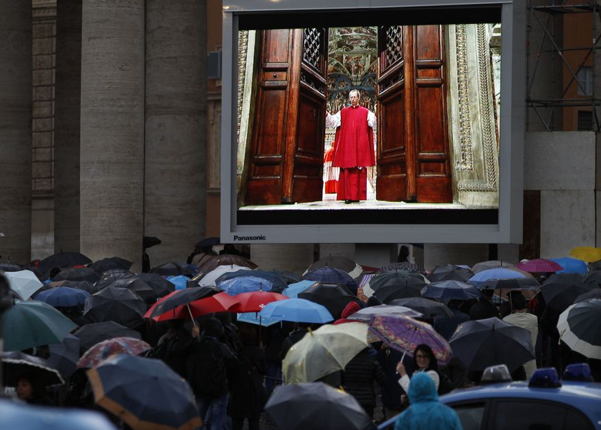 """People watch on a video monitor in St. Peter's Square as Monsignor Guido Marini, master of liturgical ceremonies, closes the double doors to the Sistine Chapel in Vatican City Tuesday, March 12, 2013, at the start of the conclave of cardinals to elect the next pope. Marini closed the doors after shouting """"Extra omnes,"""" Latin for """"all out,"""" telling everyone but those taking part in the conclave to leave the frescoed hall. He then locked it. (AP Photo/Michael Sohn)"""