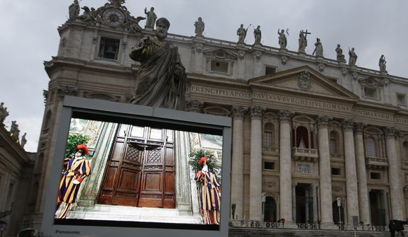 """A giant monitor in St. Peter's Square at the Vatican, Tuesday, March 12, 2013, shows the heavy wooden door to the Sistine Chapel being closed and locked, signaling the start of the conclave to elect a new pope to succeed Benedict XVI following his stunning resignation. Monsignor Guido Marini, master of liturgical ceremonies, closed the double doors after shouting """"Extra omnes,"""" Latin for """"all out,"""" telling everyone but those taking part in the conclave to leave the frescoed hall. He then locked it. (AP Photo/Gregorio Borgia)"""