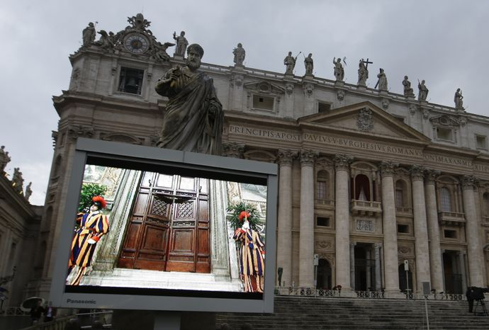 "A giant monitor in St. Peter's Square at the Vatican, Tuesday, March 12, 2013, shows the heavy wooden door to the Sistine Chapel being closed and locked, signaling the start of the conclave to elect a new pope to succeed Benedict XVI following his stunning resignation. Monsignor Guido Marini, master of liturgical ceremonies, closed the double doors after shouting ""Extra omnes,"" Latin for ""all out,"" telling everyone but those taking part in the conclave to leave the frescoed hall. He then locked it. (AP Photo/Gregorio Borgia)"