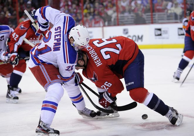 New York Rangers center Derek Stepan (21) battles for the puck against Washington Capitals center Matt Hendricks (26) during the second period of an NHL hockey game, Sunday, March 10, 2013, in Washington. (AP Photo/Nick Wass)