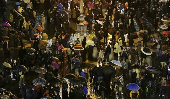 People wait in St. Peter's Square while cardinals meet in conclave to elect the next pope in the Sistine's Chapel at the Vatican, Tuesday, March 12, 2013. (AP Photo/Andrew Medichini)