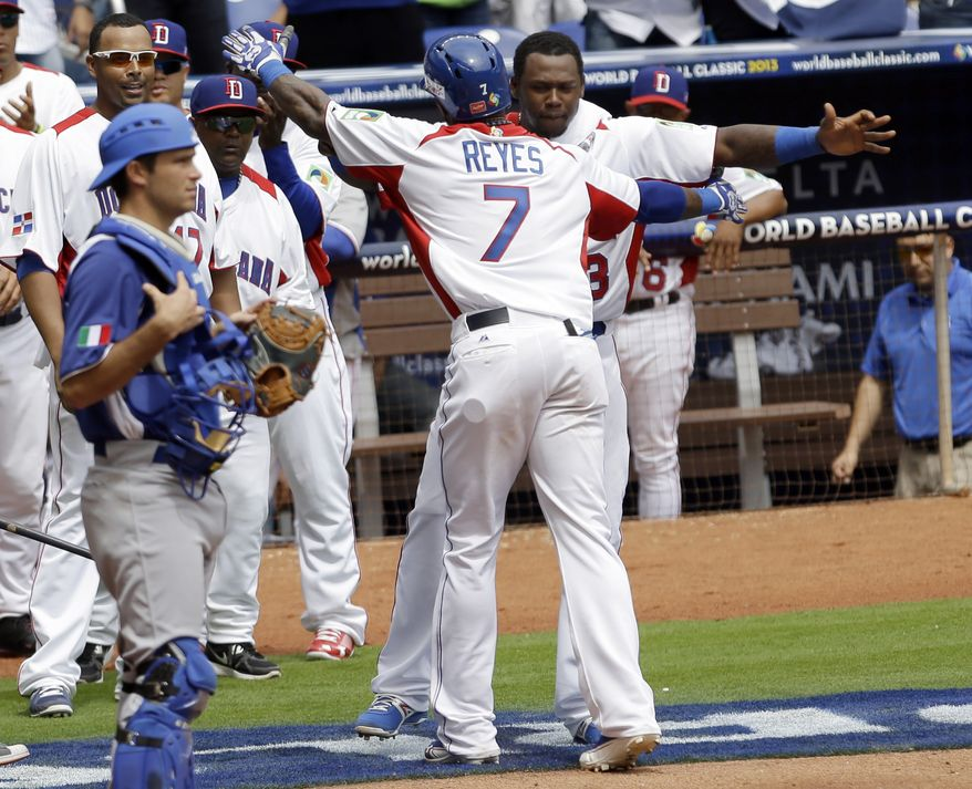 Dominican Republic's Jose Reyes (7) is congratulated by teammate Hanley Ramirez after hitting a solo home run against Italy in the third inning of the World Baseball Classic game as Italy catcher Drew Butera, left, looks on in Miami, Tuesday, March 12, 2013. (AP Photo/Alan Diaz)