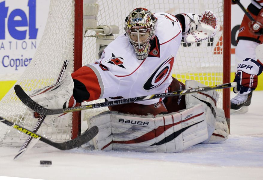 Carolina Hurricanes goalie Justin Peters reaches for the puck in the second period of the Hurricanes' 4-0 win against the Washington Capitals on March 12, 2013, in Washington. (Associated Press)