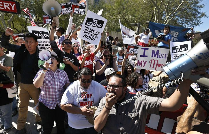 Dozens of immigration rights supporters chant during a Puente Movement event March Against Deportation, Family Separation and Workplace Raids in front of Montgomery County Attorney Bill Montgomery's office on Monday, March 11, 2013, in Phoenix. (AP Photo/Ross D. Franklin)