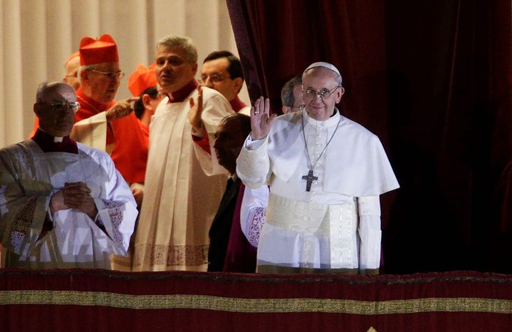 Pope Francis flanked by Monsignor Guido Marini, master of liturgical ceremonies, waves to the crowd from the central balcony of St. Peter's Basilica at the Vatican, Wednesday, March 13, 2013. Cardinal Jorge Bergoglio, who chose the name of Francis is the 266th pontiff of the Roman Catholic Church. (AP Photo/Andrew Medichini)