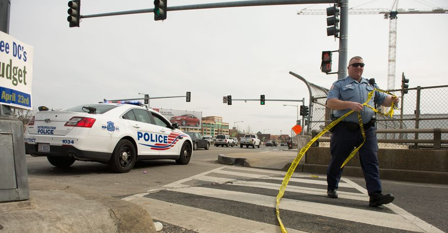 **FILE** An officer removes police tape from a crime scene. (Andrew Harnik/The Washington Times)