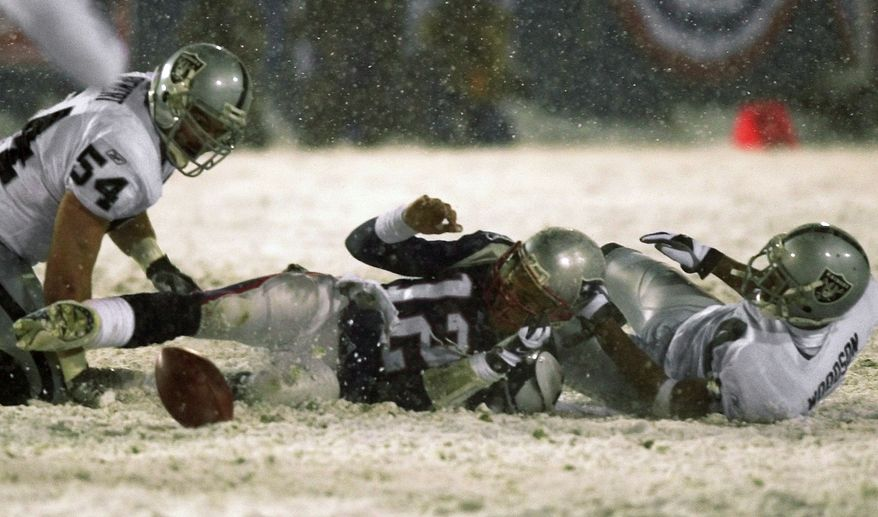 **FILE** New England Patriots quarterback Tom Brady (12) loses the ball after being brought down by Oakland Raiders' Charles Woodson, right, while Greg Biekert (54) moves to recover the ball in the fourth quarter of their AFC Division Playoff game in Foxboro, Mass. Saturday night, Jan. 19, 2002. The play was appealed, and the Patriots retained possession in the most famous example of the 'tuck rule.' The Patriots went on to win, 16-13, in overtime. (AP Photo/Elise Amendola)