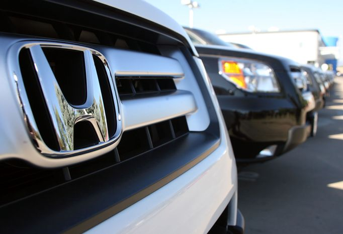 **FILE** The Honda emblem glimmers off the front of a 2007 Pilot sports utility vehicle on the lot of a Honda dealership in the south Denver suburb of Littleton, Colo., on Sept. 17, 2006. (Associated Press)