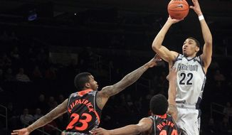 Georgetown's Otto Porter Jr. (22) shoots over Cincinnati's Sean Kilpatrick (23) and JaQuon Parker during the first half of an NCAA college basketball game at the Big East Conference tournament, Thursday, March 14, 2013 in New York. (AP Photo/Mary Altaffer)