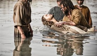 "Diogo Morgado as Jesus, center, is baptized by Daniel Percival, as John, in a scene from History's ""The Bible.""  The five-part mini-series, produced by the husband-and-wife team of Mark Burnett and Roma Downey, concluded March, 31. The producers now plan on bringing the story to the big screen. (AP Photo/History, Joe Alblas)"