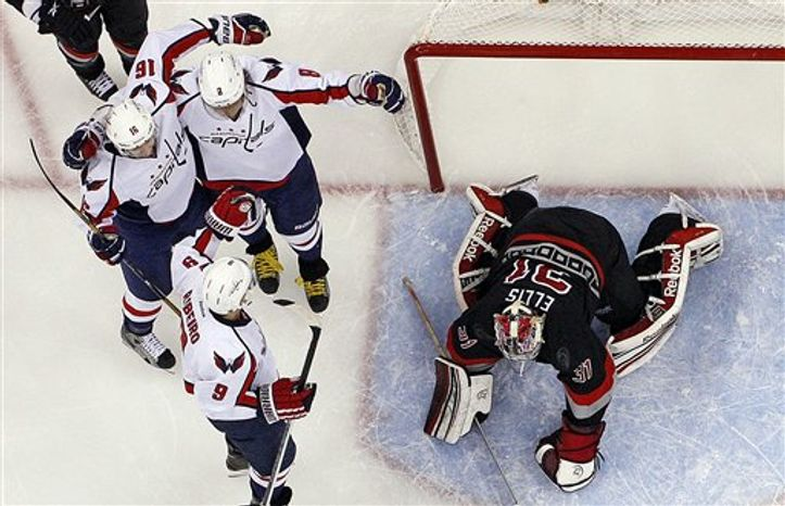 Washington Capitals' Mike Ribeiro (9) celebrates his goal with Eric Fehr (16) and Alex Ovechkin (8), of Russia, near Carolina Hurricanes goalie Dan Ellis (31) during the third period of an NHL hockey game, Thursday, March 14, 2013, in Raleigh, N.C. The Capitals won 3-2. (AP Photo/Karl B DeBlaker)