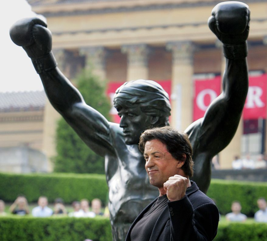 """**FILE** Actor Sylvester Stallone makes a fist in front of a bronze statue portraying the boxer Rocky Balboa from the film """"Rocky III"""" after it was unveiled near the steps of the Philadelphia Museum of Art in Philadelphia on Sept. 8, 2006. (Associated Press)"""
