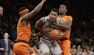 Georgetown's Mikael Hopkins, center, is defended by Syracuse's Baye Keita, right, and Syracuse's C.J. Fair, left, during the first half of an NCAA college basketball game at the Big East Conference tournament Friday, March 15, 2013, in New York. (AP Photo/Frank Franklin II)