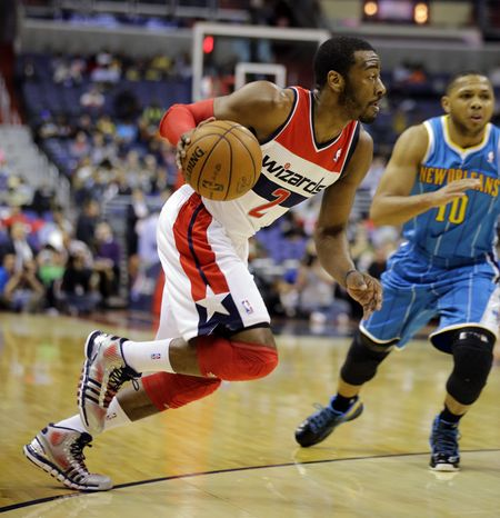 Washington Wizards guard John Wall (2) drives with the ball with New Orleans Hornets guard Eric Gordon (10) nearby, in the first half of an NBA basketball game Friday, March 15, 2013 in Washington. (AP Photo/Alex Brandon)