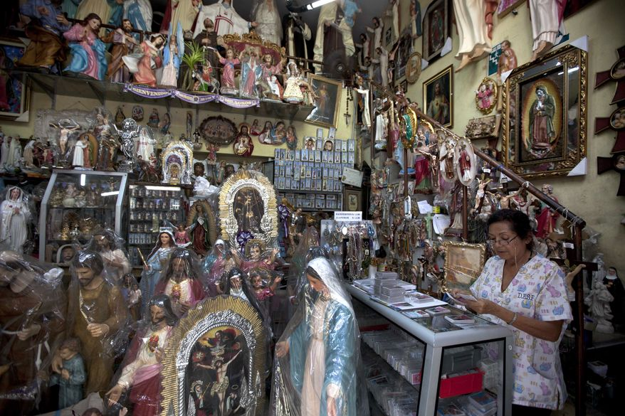 Maria Villena looks at inventory at a store that sells Catholic iconography in Lima, Peru, Wednesday, March 13, 2013. (AP Photo/Martin Mejia)