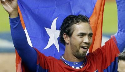 Puerto Rico pitcher Nelson Figueroa holds up his flag as he celebrates after Puerto Rico defeated the United States 4-3 during a second-round elimination game of the World Baseball Classic, Friday, March 15, 2013, in Miami. (AP Photo/Wilfredo Lee)
