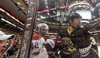 As fans look on, Boston Bruins defenseman Zdeno Chara, right, of Slovakia, checks Washington Capitals right wing Joel Ward (42) into the boards during the third period of Boston's 4-1 win in an NHL hockey game in Boston, Saturday, March 16, 2013. (AP Photo/Winslow Townson)