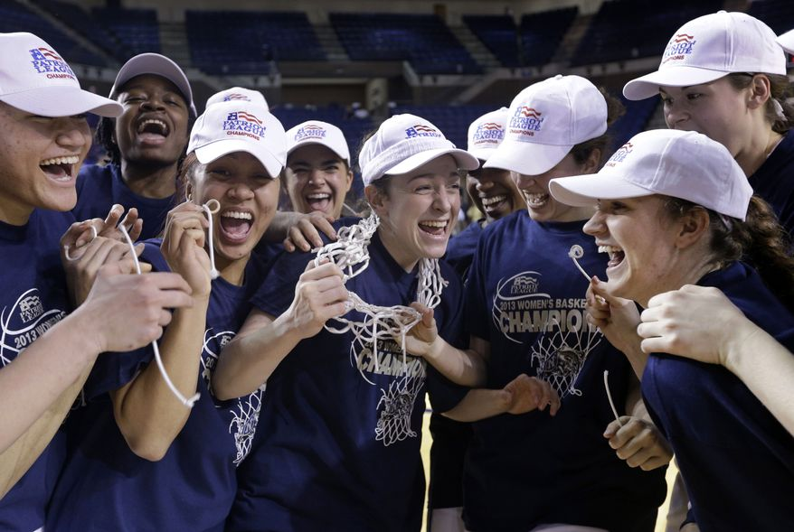 Navy guard Kara Pollinger, center, celebrates with teammates after they cut the net after an NCAA college basketball game against Holy Cross in the championship of the Patriot League conference tournament in Annapolis, Md., Saturday, March 16, 2013. Pollinger contributed a game-high 24 points to Navy's 72-53 win. (AP Photo/Patrick Semansky)