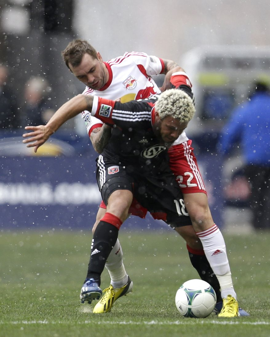 D.C. United midfielder Nick DeLeon, front, shields the ball from New York Red Bulls midfielder Jonny Steele during the first half of an MLS soccer game, Saturday, March 16, 2013, in Harrison, N.J. (AP Photo/Julio Cortez)