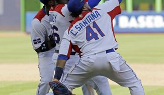 Dominican Republic's Carlos Santana (41), Fernando Rodney, center, and Robinson Cano celebrate their 2-0 win over Puerto Rico during the second-round game final of the World Baseball Classic in Miami, Saturday, March 16, 2013. (AP Photo/Alan Diaz)