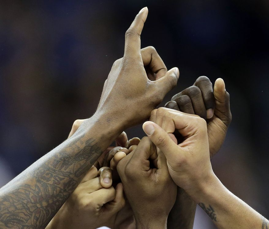 Kansas players celebrate their 70-54 win over Kansas State in their NCAA college Big 12 tournament championship basketball game, Saturday, March 16, 2013, in Kansas City, Mo. (AP Photo/Charlie Riedel)