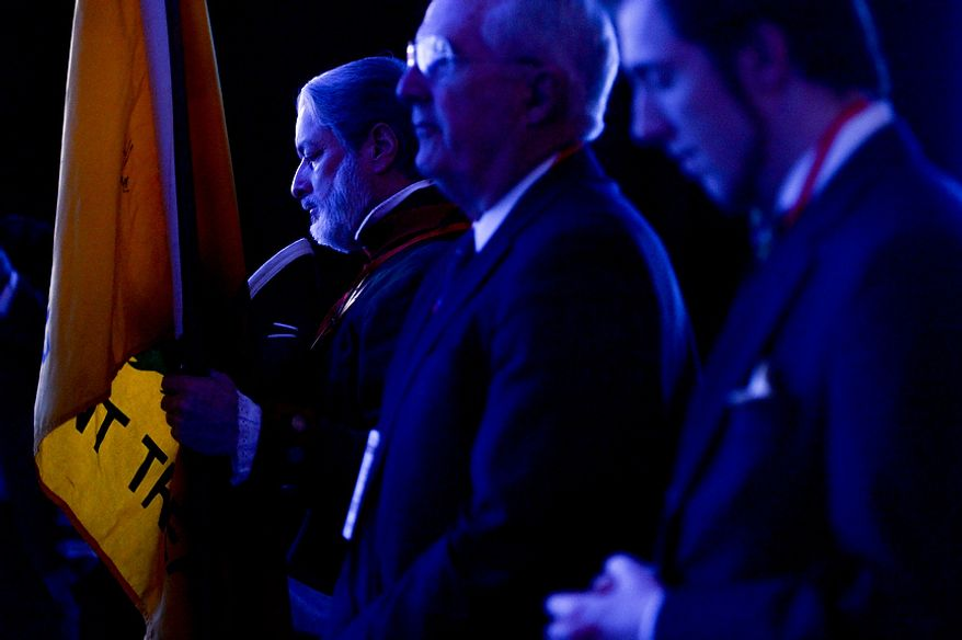 Tea Party member William Temple of Brunswick, Ga., left, who dresses as Button Gwinnett, a representative of Georgia who was the second to sign the Declaration of Independence, listens with others to the opening day invocation at this year's Conservative Political Action Conference (C.P.A.C.) held at the Gaylord National Hotel, National Harbor, Md., Thursday, March 14, 2013. (Andrew Harnik/The Washington Times)