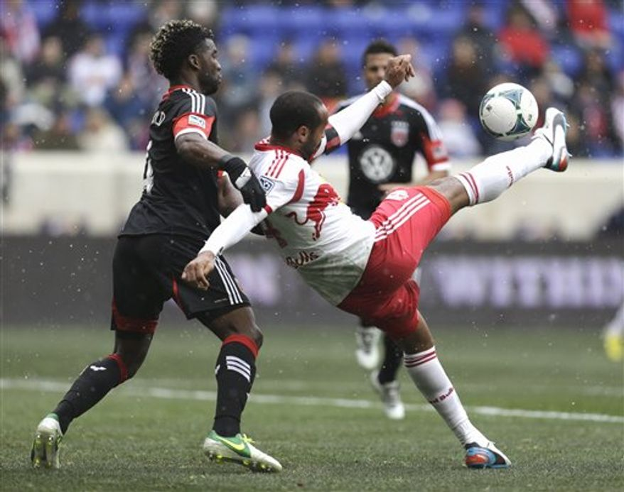 New York Red Bulls forward Thierry Henry, right, kicks the ball as D.C. United midfielder Brandon McDonald defends during the first half of an MLS soccer game, Saturday, March 16, 2013, in Harrison, N.J. (AP Photo/Julio Cortez)