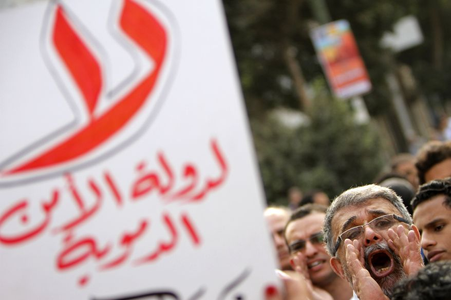 "** FILE ** An Egyptian protester shouts slogans as another holds an anti-Muslim Brotherhood banner reading, ""No for bloody state security,"" in Cairo on Saturday, March 2, 2013, during a protest in support of victims of clashes in the Nile Delta city of Mansoura the day before. (AP Photo/Amr Nabil)"
