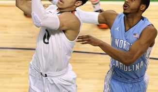 Miami's Shane Larkin makes a shot in front of North Carolina State's Dexter Strickland in the first half of an NCAA basketball game during the championship game of the ACC Tournament in Greensboro, N.C. on Sunday March 17, 2013. (AP Photo/Burlington Times-News, Al Drago)