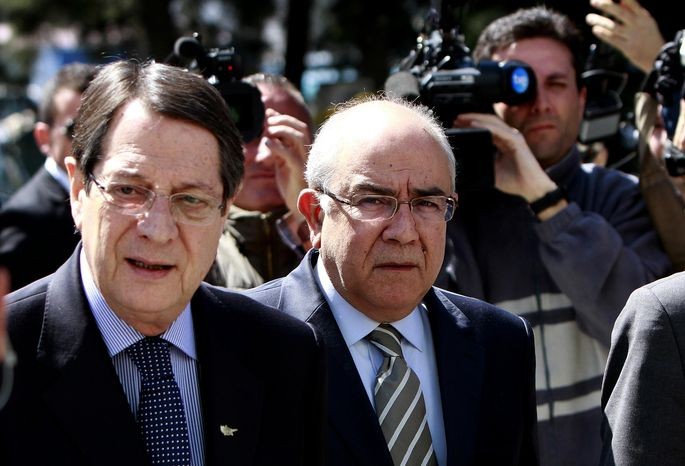 Cypriot President Nicos Anastasiades, left, and President of the Parliament Yiannakis Omirou walk toward the parliament following a meeting in capital Nicosia, Cyprus, Monday, March 18, 2013. Cyprus' president is briefing lawmakers ahead of a crucial parliamentary vote on a controversial levy on bank deposits that the cash-strapped country's creditors have demanded in exchange for a euro10 billion (US$13 billion) rescue package.(AP Photo/Petros Karadjias)
