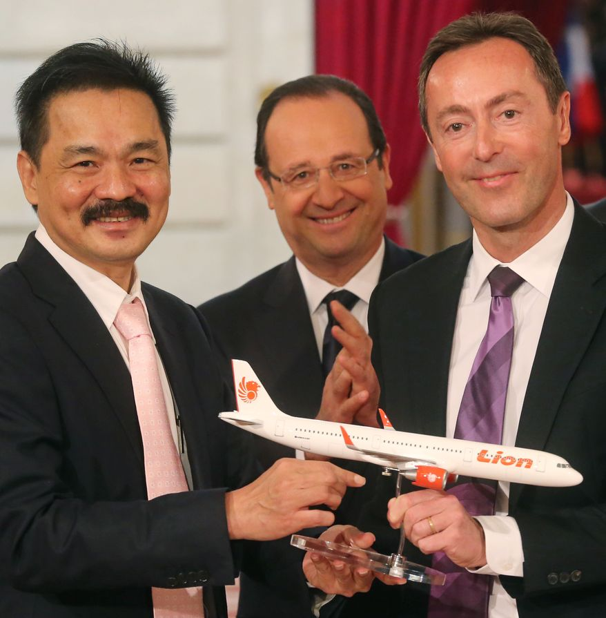 Rusdi Kirana (left), CEO of Lion Air, and Fabrice Bregier (right), CEO of Airbus, pose with an Airbus A320 model while French President Francois Hollande stands behind during a contract-signing ceremony at the Elysee Palace in Paris on Monday, March 18, 2013. Indonesian carrier Lion Air is to buy 234 short- to medium-range aircraft from Airbus for 18.4 billion euros ($24 billion) in what is being billed as the biggest civilian deal in the history of the aircraft manufacturer. (AP Photo/Michel Euler)