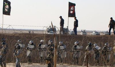 **FILE** Iraqi police stand guard outside Camp Ashraf, northeast of Baghdad, in December 2011. (Associated Press/People's Mujahedeen Organization of Iran)
