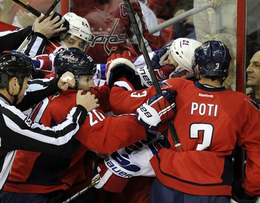 Washington Capitals right wing Troy Brouwer (20) and Tom Poti (3) scuffle with New York Rangers center Derek Stepan (21) and Ryan Callahan (24) during the third period of an NHL hockey game on Sunday, March 10, 2013, in Washington. The Rangers won 4-1. (AP Photo/Nick Wass)