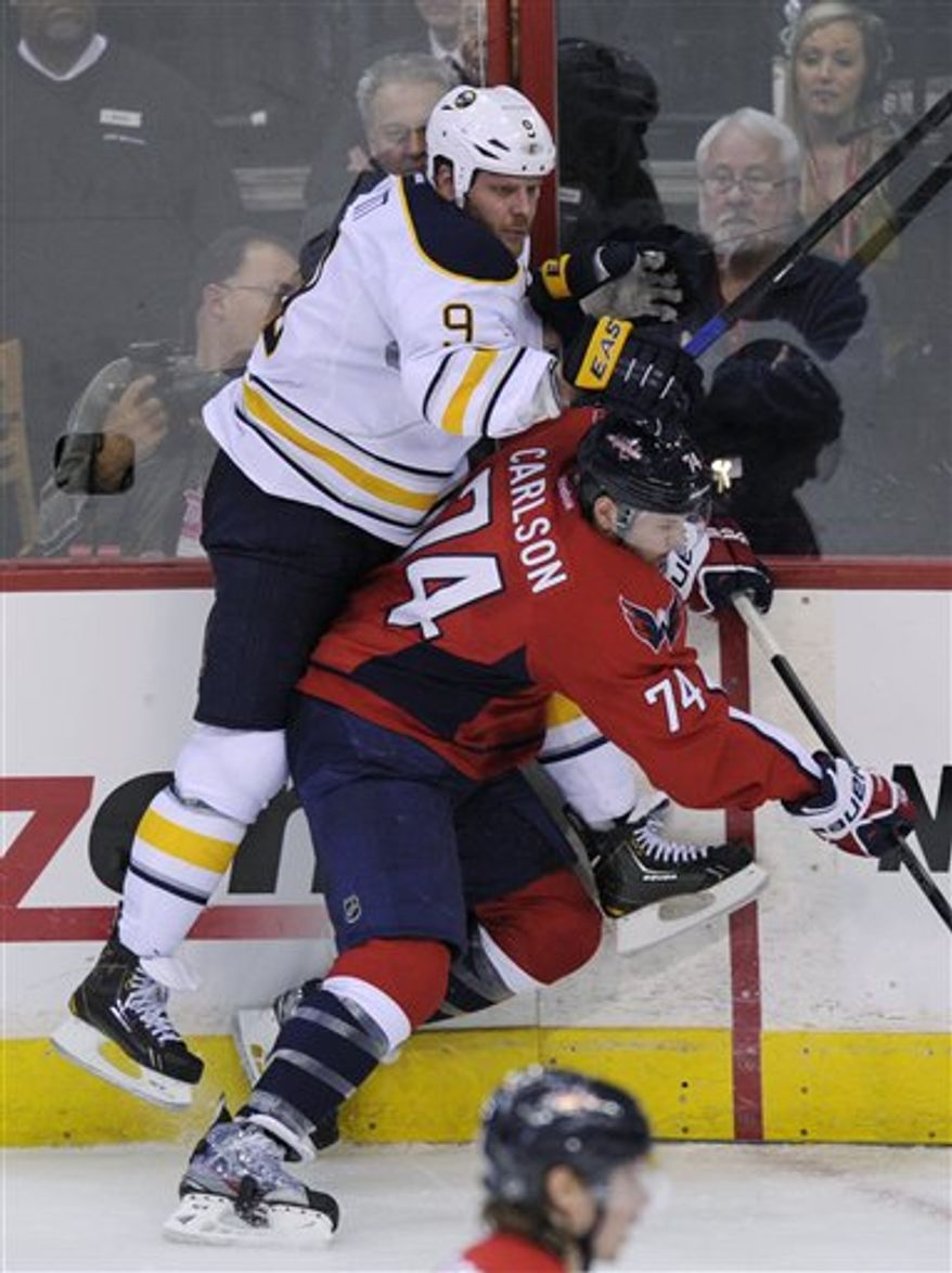 Washington Capitals defenseman John Carlson (74) collides with Buffalo Sabres center Steve Ott (9) against the boards during the third period of an NHL hockey game, Sunday, March 17, 2013, in Washington. The Capitals won 5-3. (AP Photo/Nick Wass)