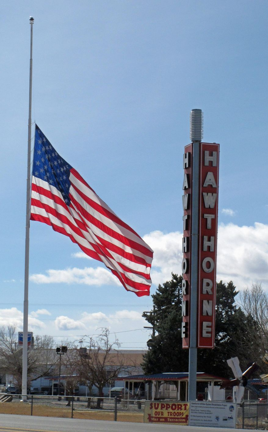 An American flag waves at half staff in Hawthorne, Calif., not far from the Army depot where seven Marines were killed and others seriously injured late Monday when a 60 mm mortar exploded during a training exercise. The Pentagon suspended use of the mortars until a review is complete. (Associated Press)