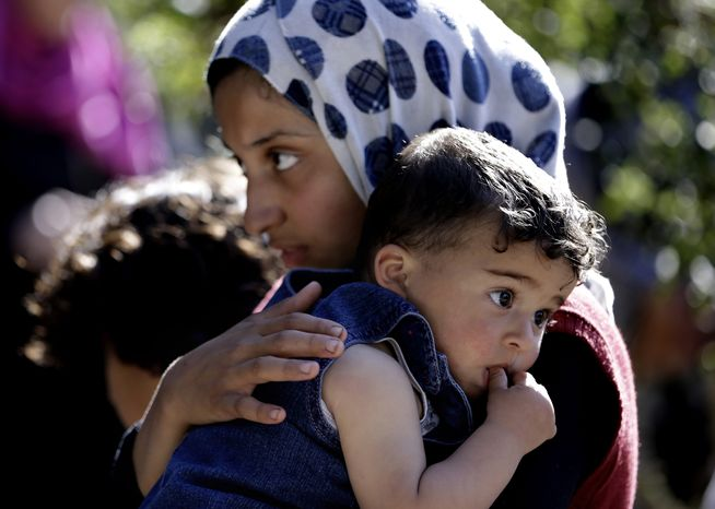 A Syrian refugee girl carries her sister March 14, 2013, as she listens to the United Nations High Commissioner for Refugees chief Antonio Guterres during his visit to a Syrian refugee camp in Ketermaya village southeast of Beirut. (Associated Press)