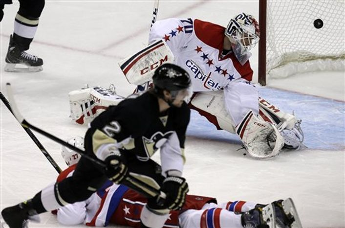 Pittsburgh Penguins defenseman Matt Niskanen (2) puts the puck behind Washington Capitals goalie Braden Holtby (70) and Washington Capitals defenseman Karl Alzner (27) for a game-winning goal in the third-period goal of an NHL hockey game in Pittsburgh Tuesday, March 19, 2013. The Penguins won 2-1. (AP Photo/Gene J. Puskar)