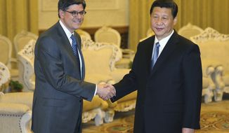 Chinese President Xi Jinping (right) shakes hands with U.S. Treasury Secretary Jack Lew during the American official's visit to the Great Hall of the People on Tuesday, March 19, 2013, in Beijing. Mr. Xi said China wants strong ties with Washington as he held talks with Mr. Lew in Mr. Xi's first meeting with a foreign official since being appointed president. (AP Photo/Feng Li, Pool)