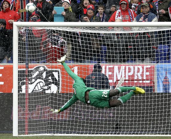 D.C. United goalkeeper Bill Hamid dives as a shot by New York Red Bulls midfielder Eric Alexander goes wide of the goal during the second half of an MLS soccer game, Saturday, March 16, 2013, in Harrison, N.J. The teams tied 0-0. (AP Photo/Julio Cortez)