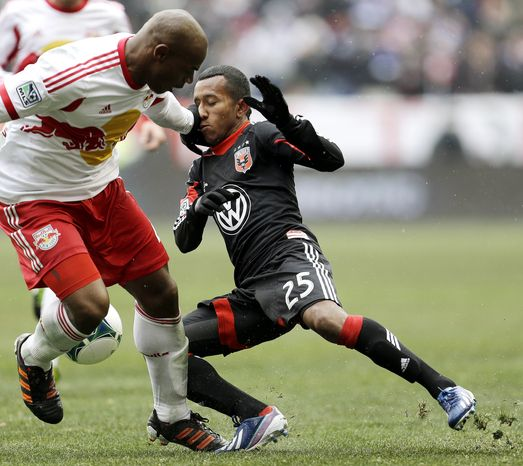 D.C. United midfielder Marcos Sanchez (25) gets a hand to the face by New York Red Bulls defender Jamison Olave during the second half of an MLS soccer match, Saturday, March 16, 2013, in Harrison, N.J. The teams tied 0-0. (AP Photo/Julio Cortez)