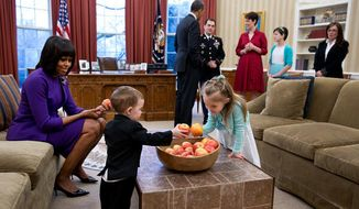 """First lady Michelle Obama and President Obama are shown during """"snack time"""" in the Oval Office. The photo was tweeted by Obama's former campaign arm, now known as Organizing for Action."""