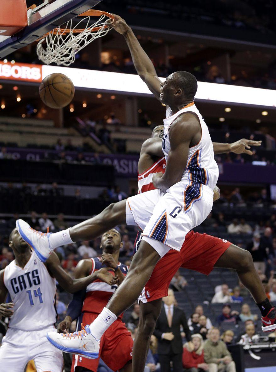 Charlotte Bobcats' Bismack Biyombo, right, dunks on Washington Wizards' Emeka Okafor, right, during the first half of an NBA basketball game in Charlotte, N.C., Monday, March 18, 2013. (AP Photo/Chuck Burton)