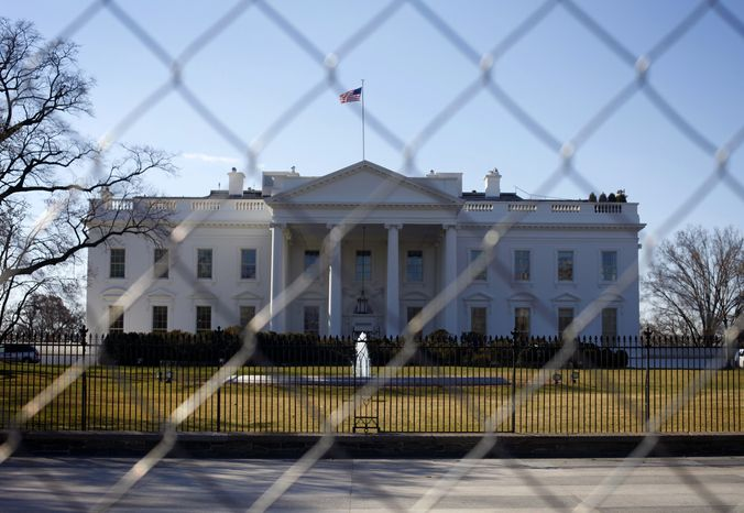 **FILE** The White House is seen through a chain-link fence where the inaugural reviewing stand once stood in Washington on March 4, 2013. (Associated Press)