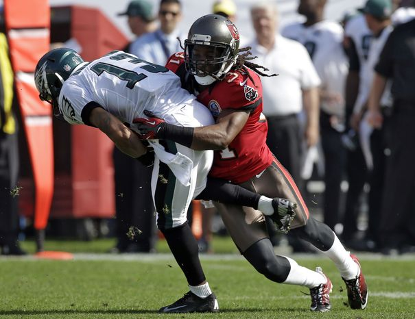 **FILE** Tampa Bay Buccaneers cornerback E.J. Biggers (31) takes down Philadelphia Eagles wide receiver Damaris Johnson (13) after a short reception during the first quarter of an NFL football game Sunday, Dec. 9, 2012, in Tampa, Fla. (AP Photo/Chris O'Meara)